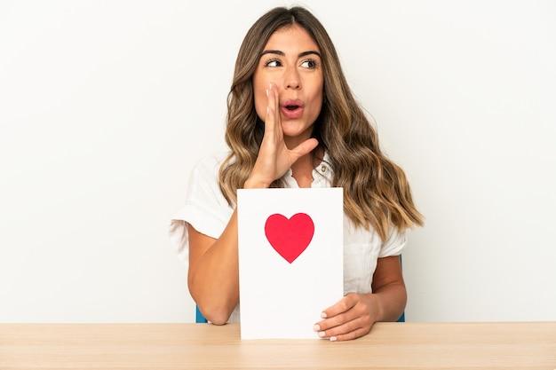 La giovane donna caucasica che tiene una carta di san valentino isolata sta dicendo una notizia di frenata calda segreta e sta guardando da parte