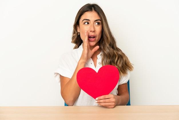 La giovane donna caucasica che tiene un cuore di san valentino isolato sta dicendo una notizia di frenata calda segreta e sta guardando da parte
