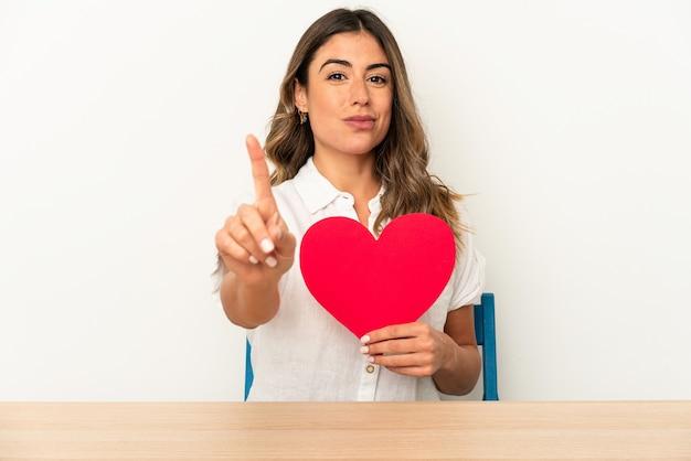 Giovane donna caucasica che tiene un cuore di san valentino isolato che mostra il numero uno con il dito.