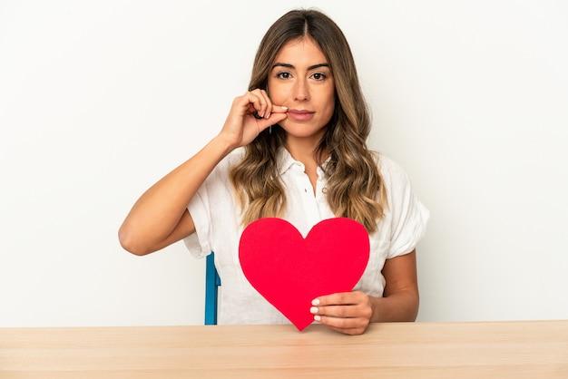 Giovane donna caucasica che tiene un cuore di san valentino isolato con le dita sulle labbra mantenendo un segreto.