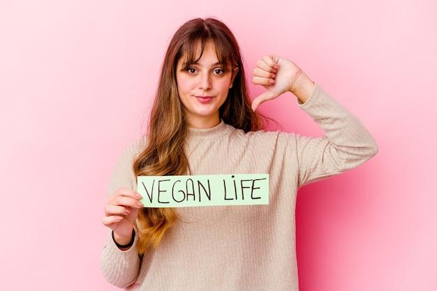 Giovane donna caucasica che tiene un cartello di vita vegano isolato che mostra un gesto di avversione, pollice in giù. concetto di disaccordo.