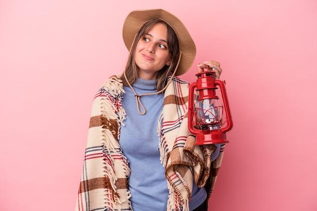 Giovane donna caucasica che tiene lanterna vintage isolata su sfondo rosa sognando di raggiungere obiettivi e scopi
