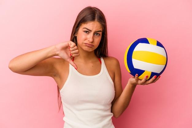 Giovane donna caucasica che tiene una palla da pallavolo isolata su sfondo rosa che mostra un gesto di antipatia, pollice in giù. concetto di disaccordo.