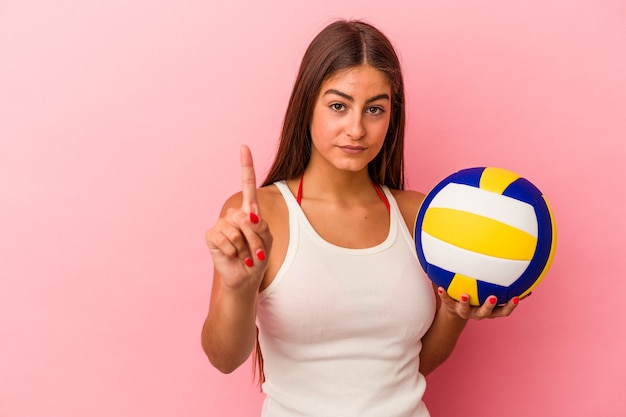 Giovane donna caucasica che tiene una palla da pallavolo isolata su sfondo rosa che mostra il numero uno con il dito.