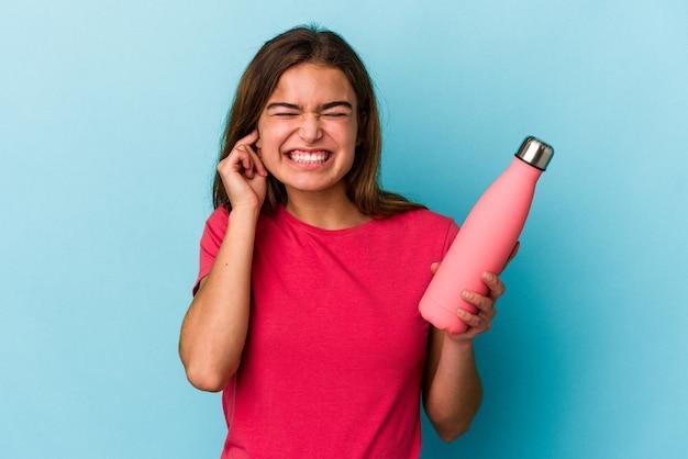 Giovane donna caucasica che tiene una bottiglia d'acqua isolata su sfondo blu che copre le orecchie con le mani.