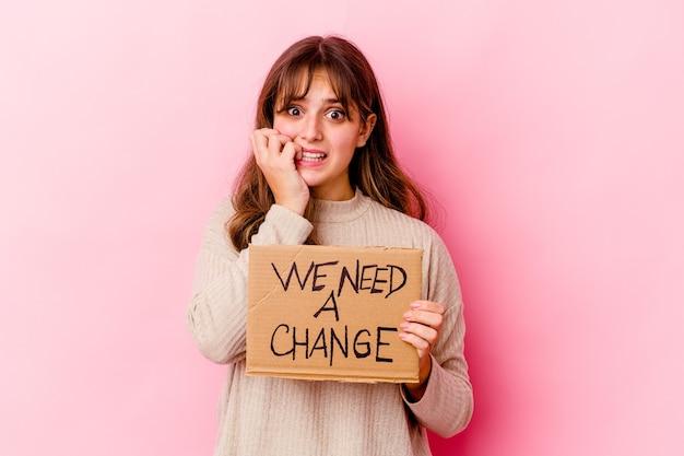 Giovane donna caucasica che tiene un abbiamo bisogno di un banner di cambiamento