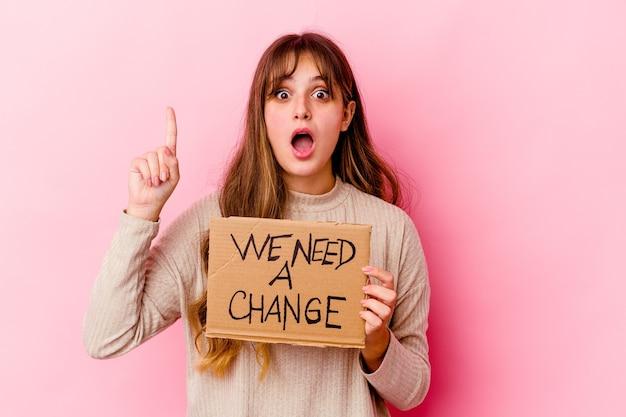 Giovane donna caucasica che tiene un abbiamo bisogno di un cartello di cambiamento isolato avendo un'idea, un concetto di ispirazione.