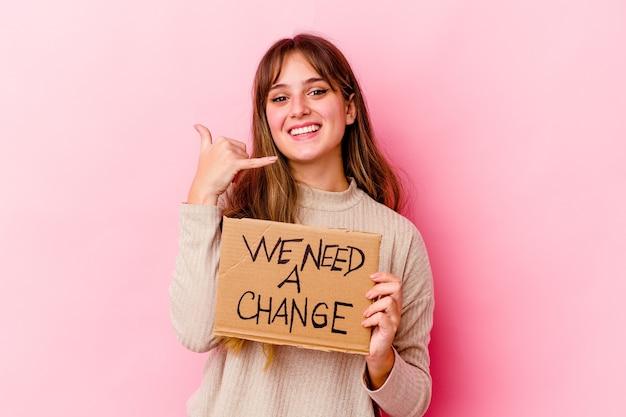 Giovane donna caucasica che tiene un abbiamo bisogno di un cartello di cambiamento isolato che mostra un gesto di chiamata di telefono cellulare con le dita.