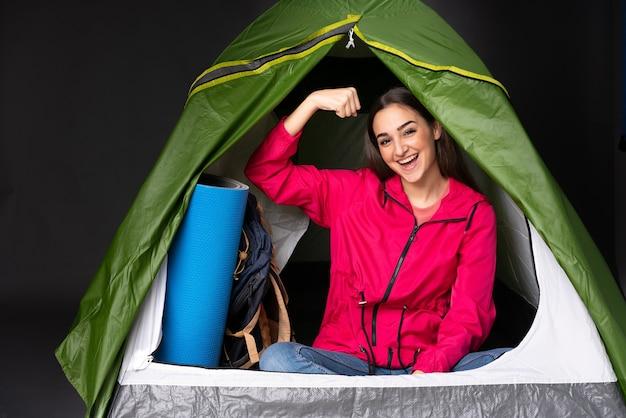 Giovane donna caucasica all'interno di una tenda da campeggio verde facendo un forte gesto