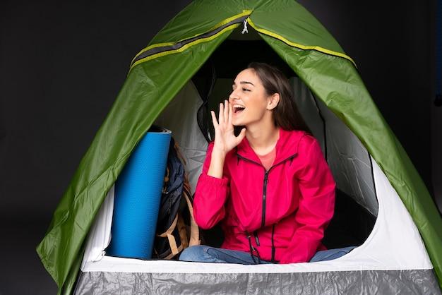 Giovane donna caucasica all'interno di una tenda da campeggio verde che grida con la bocca spalancata sul lato