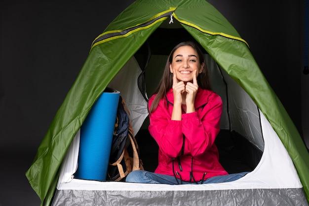 Giovane donna caucasica all'interno di una tenda da campeggio verde sorridente con un'espressione felice e piacevole