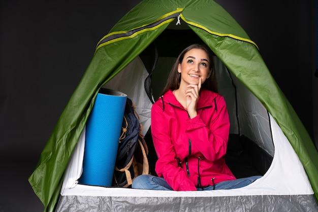 Giovane donna caucasica all'interno di una tenda da campeggio verde pensando a un'idea mentre osservava