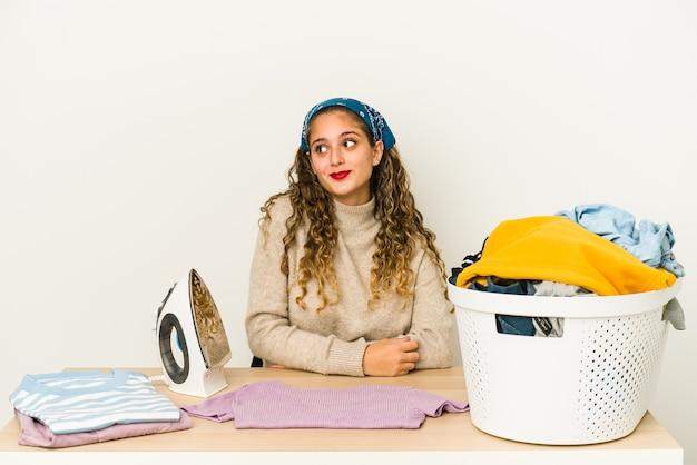 La giovane donna caucasica stirare i vestiti ha isolato il sogno di raggiungere obiettivi e scopi