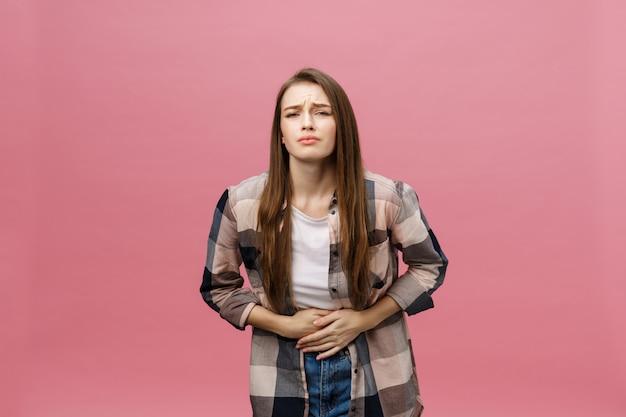 Giovane donna caucasica su sfondo isolato con la mano sullo stomaco