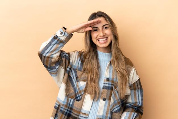 Giovane donna caucasica isolata su fondo beige che saluta con la mano con espressione felice