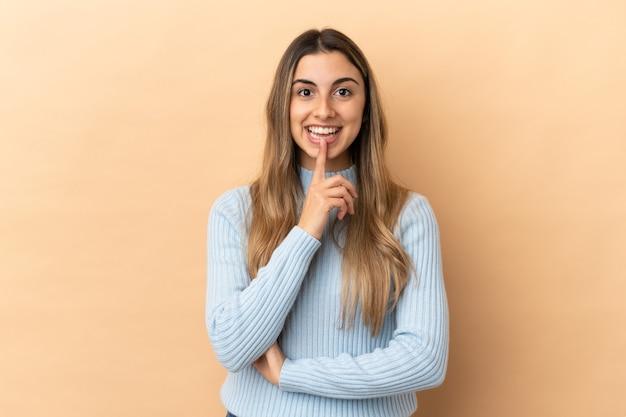Giovane donna caucasica isolata su sfondo beige che mostra un segno di gesto di silenzio mettendo il dito in bocca