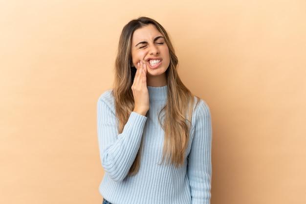 Giovane donna caucasica isolata su sfondo beige con mal di denti