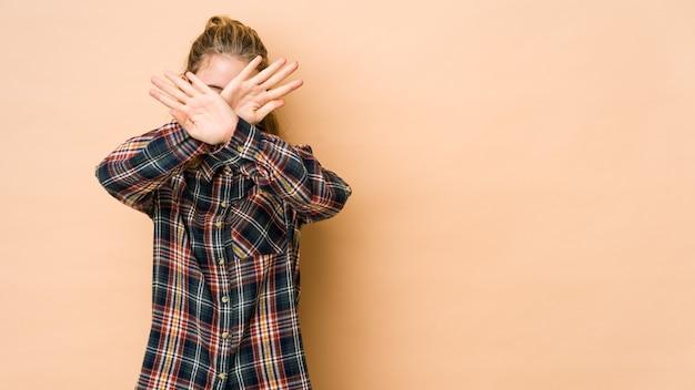 Giovane donna caucasica isolata sul beige mantenendo due braccia incrociate, concetto di rifiuto.