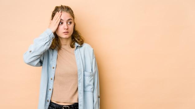 Giovane donna caucasica isolata sulla parete beige che è scioccata, ha ricordato un incontro importante.