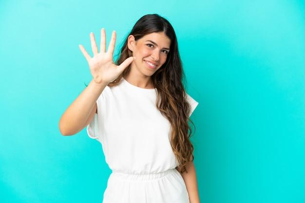 Giovane donna caucasica isolata su sfondo blu contando cinque con le dita