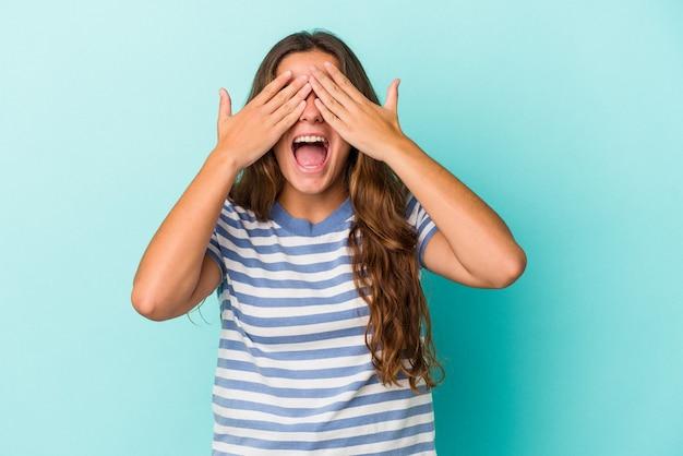 La giovane donna caucasica isolata su fondo blu copre gli occhi con le mani, sorride ampiamente in attesa di una sorpresa.