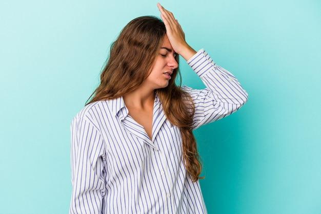 Giovane donna caucasica isolata su sfondo blu dimenticando qualcosa, schiaffeggiando la fronte con il palmo e chiudendo gli occhi.