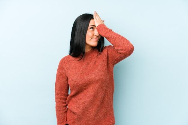 Giovane donna caucasica isolata su sfondo blu dimenticando qualcosa, schiaffi sulla fronte con il palmo e chiudendo gli occhi.
