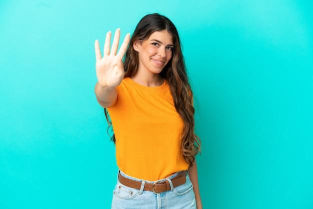 Giovane donna caucasica isolata su sfondo blu felice e contando quattro con le dita