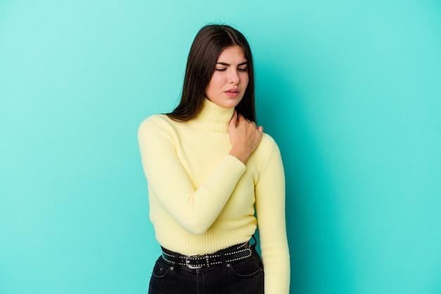 Giovane donna caucasica isolata su priorità bassa blu che ha un dolore alla spalla.