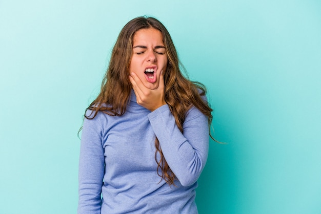 Giovane donna caucasica isolata su sfondo blu con un forte dolore ai denti, dolore molare.