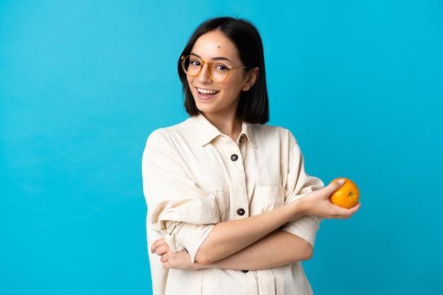 Giovane donna caucasica isolata su priorità bassa blu che tiene un'arancia