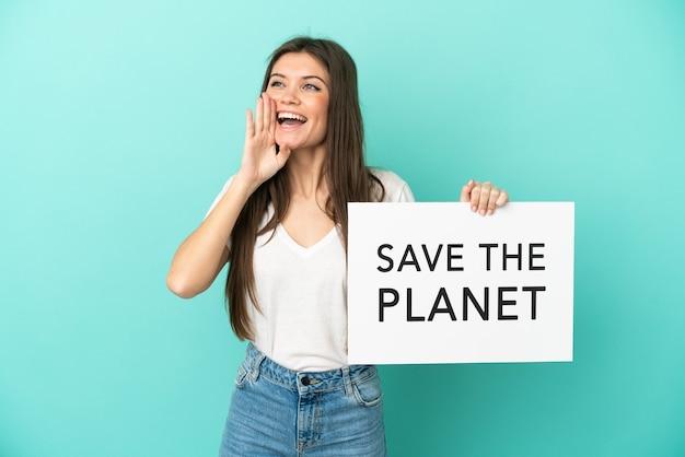 Giovane donna caucasica isolata su sfondo blu che tiene un cartello con il testo salva il pianeta e urla