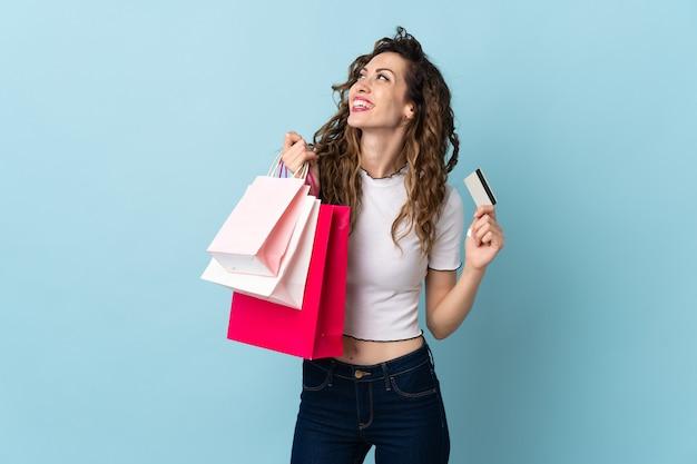 Giovane donna caucasica isolata su sfondo blu tenendo le borse della spesa e una carta di credito