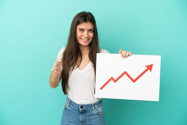 Giovane donna caucasica isolata su sfondo blu con in mano un cartello con un simbolo di freccia di statistiche in crescita che fa un accordo