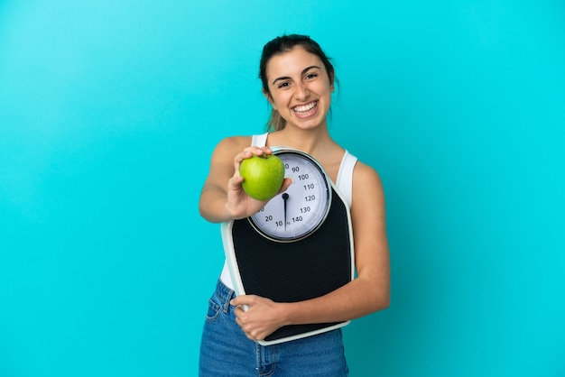 Giovane donna caucasica isolata su sfondo blu che tiene in mano una bilancia e offre una mela