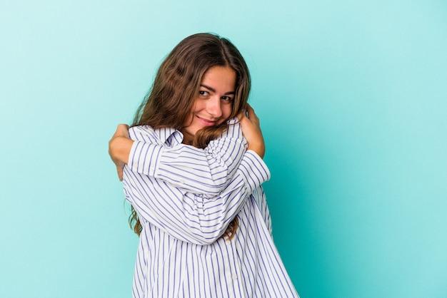 La giovane donna caucasica isolata sugli abbracci blu del fondo, sorride spensierata e felice.
