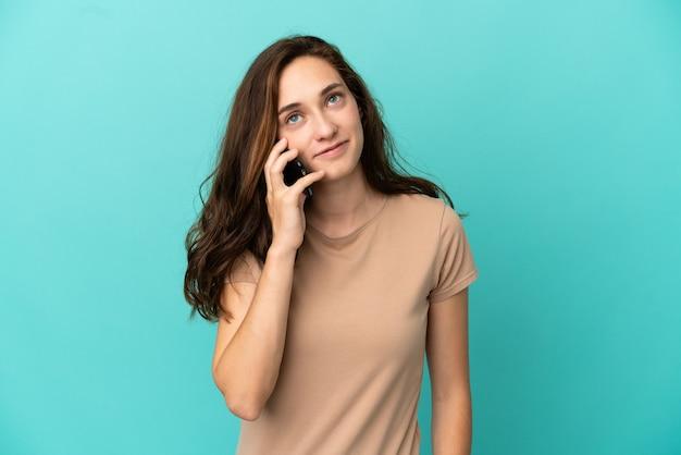 Giovane donna caucasica isolata su sfondo blu che tiene una conversazione con il telefono cellulare con qualcuno