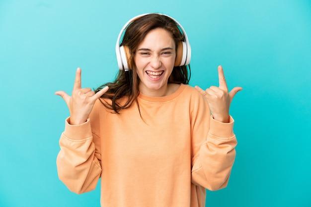 Giovane donna caucasica isolata su sfondo blu ascoltando musica che fa gesto rock