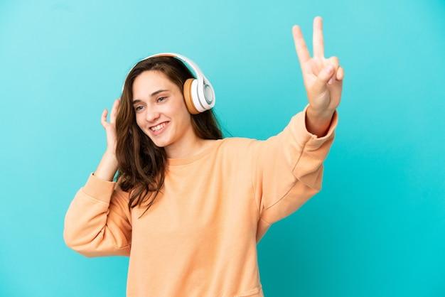 Giovane donna caucasica isolata su sfondo blu ascoltando musica e cantando