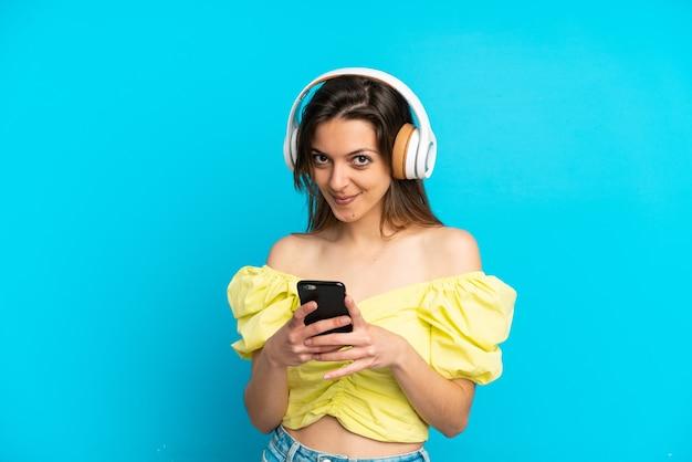 Giovane donna caucasica isolata su sfondo blu ascoltando musica con un cellulare e guardando davanti