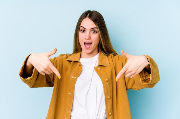 Giovane donna caucasica isolata su sfondo blu punta verso il basso con le dita, sensazione positiva.