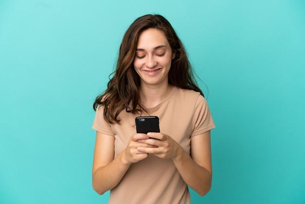 Giovane donna caucasica isolata su sfondo blu che invia un messaggio o un'e-mail con il cellulare
