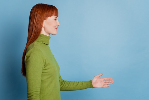 Giovane donna caucasica su sfondo blu isolato che stringe la mano