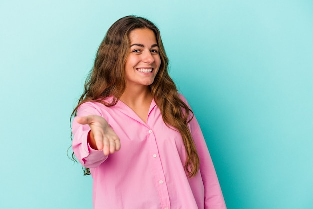 Giovane donna caucasica isolata su fondo blu che allunga la mano alla macchina fotografica nel gesto di saluto.