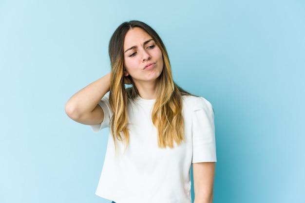 Giovane donna caucasica isolata su sfondo blu soffre di dolore al collo a causa di uno stile di vita sedentario.