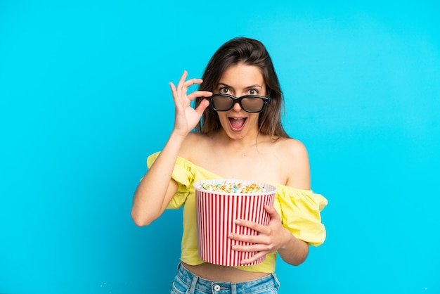 Giovane donna caucasica isolata su sfondo blu sorpresa con occhiali 3d e con in mano un grande secchio di popcorn