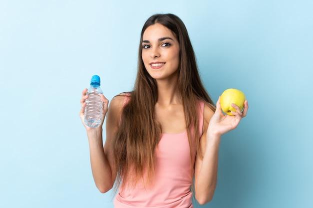 Giovane donna caucasica isolata su sfondo blu con una mela e con una bottiglia d'acqua