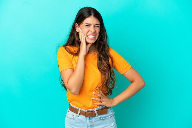 Giovane donna caucasica isolata su sfondo blu con mal di denti