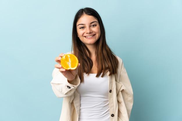 Giovane donna caucasica isolata sull'azzurro che tiene un'arancia