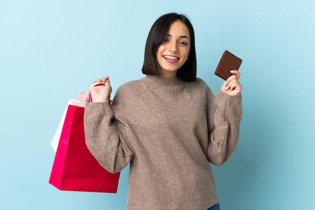 Giovane donna caucasica isolata sui sacchetti della spesa blu della tenuta e una carta di credito